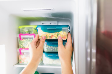 Woman taking container with frozen mixed vegetables from freezer.