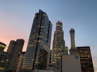 LOS ANGELES, CA, JAN 2020: Downtown skyscrapers at dusk with lights on top of US Bank Tower showing purple and yellow, LA Lakers basketball team colors in memory of player Kobe Bryant