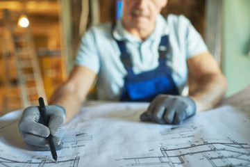 Close up of senior construction worker looking at floor plans while renovating house, copy space