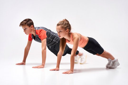 Energizing lives. Full-length shot of teenage boy and girl engaged in sport, looking away while doing push-ups. Isolated on white background. Training, active lifestyle, team concept