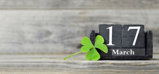 St Patricks Day background or banner with copy space. Vintage calendar and shamrock on wooden background