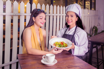 Young waitress serving salad on plate to customer