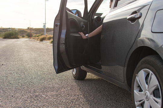 Woman with opened door getting out of the carn on the road