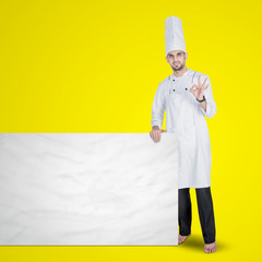 Young chef showing ok gesture with blank board