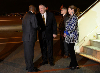 U.S. Secretary of State Mike Pompeo (C) and his wife Susan are greeted by Angolan Foreign Minister Manuel Domingos Augusto (L) at 4 de Fevereiro International Airport in Luanda