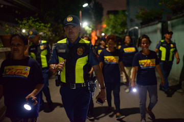 Members of a volunteer group of women patrol with police officers on the streets of Pateros