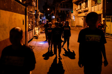Members of a volunteer group of women patrol with police officers on the streets of Pateros, Metro Manila