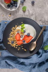 Ripe blueberries and strawberries with yogurt and granola