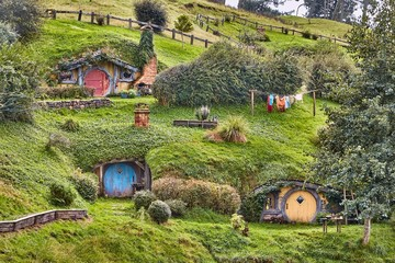 MATAMATA, NEW ZEALAND - CIRCA 2016: Movie set for the Lord of The Rings and The Hobbit. Hobbit holes in the hillside of the Shire, circular doors