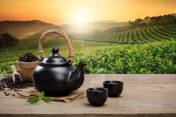 Poster de jardin The Cup of hot tea with teapot, green tea leaves and dried herbs on the wooden table in plantations background with empty space, Organic product from the nature for healthy with traditional