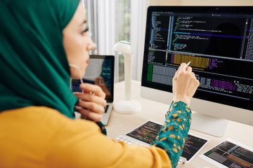 Young muslim software developer checking strings in programming code on computer screen