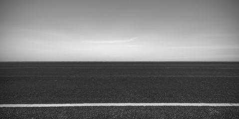 Side view of asphalt road with dark sky background