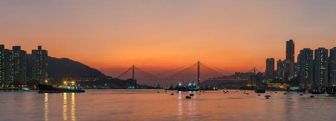 Fototapete - Panorama of idyllic landscape of harbor of Hong Kong city under sunset