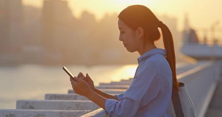 Wall Mural - Woman use of cellphone under sunset in Hong Kong