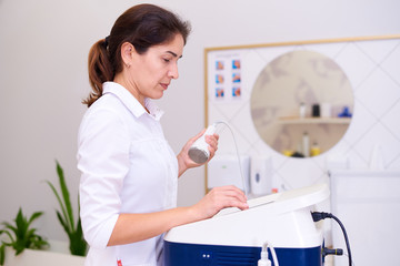 A doctor with a cavitation apparatus in a cosmetology clinic.