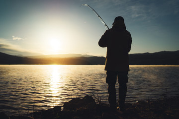 silhouette fisherman with fishing rod at sunrise sunlight, outline man enjoy hobby sport on evening...