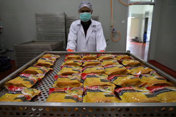 A worker moves food packages inside Mychef halal food factory in Kuala Lumpur