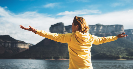 happy tourist traveler stand with raised hands, girl hiker enjoying mountains lake with arms outstretched breathing of fresh clean air in trip in spain, relax holiday Fotomurales
