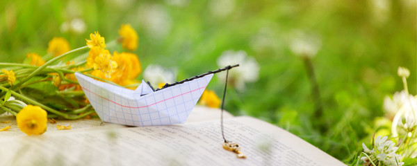 Open book outdoor. Knowledge is power. Book in a spring summer forest or garden, yard, concept of studying, dreaming, rest time, romance relax, banner