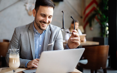 Wall Mural - Happy confident businessman working, using laptop in office