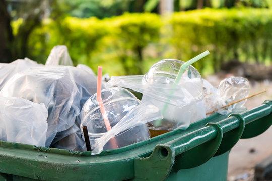 Single-use plastic cups in garbage bin