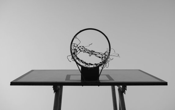 Black and white tone of Old basketball hoop on sky background in the public stadium.