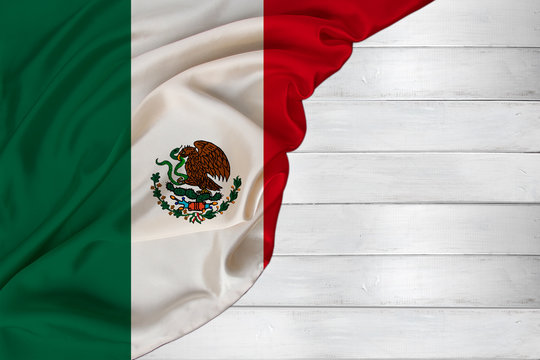 horizontal colored national flag of the modern state of Mexico, beautiful silk, white wood background, concept of tourism, economy, politics, emigration, independence day, copy space, template