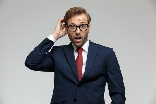 businessman standing and scratching his head shocked