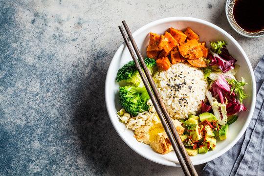 Vegan rice and vegetables salad. Macrobiotic set with rice, hummus, avocado, broccoli and sweet potato.