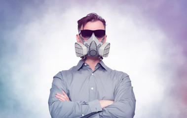Serious man in respirator and sunglasses stands with his hands folded over his chest. Smoke around. Virus protection concept