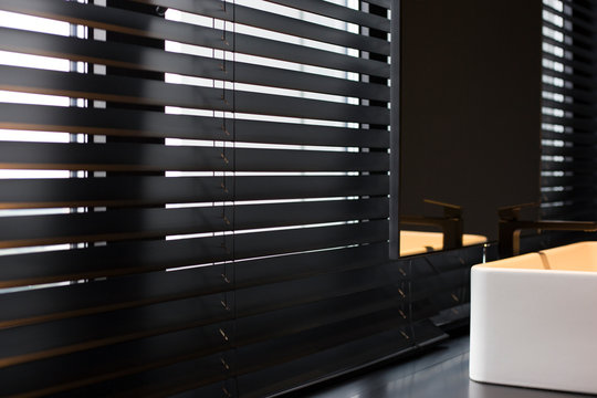 Wood blinds Coulisse black color closeup on the window. Wooden plate 50mm wide. Venetian blinds in the bathroom. Black tap, mirror near the washbasin.