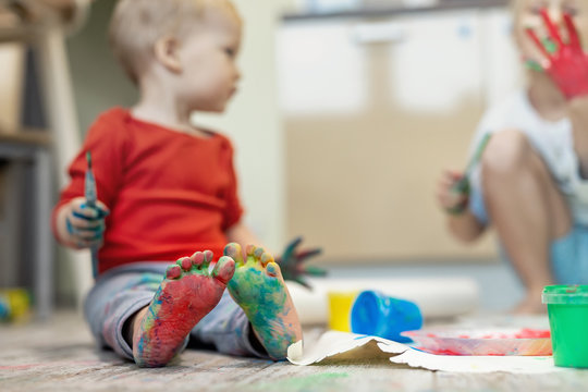 Adorable cute caucasian little blond siblings children enjoy having fun painting with brush and palm at home indoors . Cheerful happy kids smiling drawing masterpiece art picture. Messy dirty room
