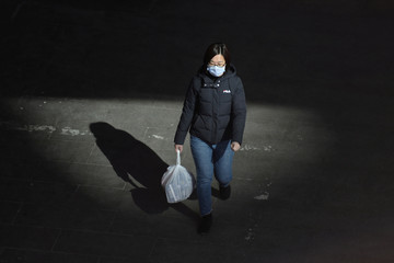 Woman wearing a face mask walks on a street with a bag of goods, as the country is hit by an outbreak of the novel coronavirus, in Beijing's tech hub Zhongguancun