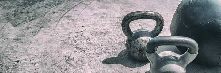 Gym fitness center header background panorama banner. Free weights kettlebell and medicine ball for training workout texture. Kettlebells heavy weight for weightlifting cross training panoramic.