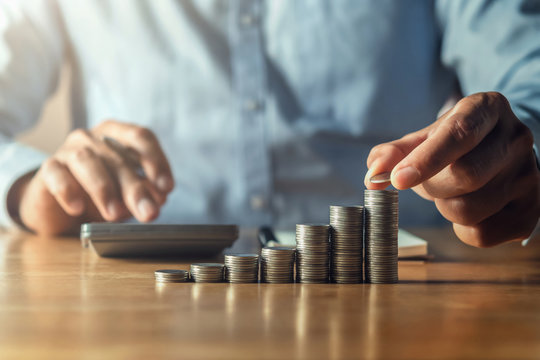 saving money with hand putting coins on stack concept financial