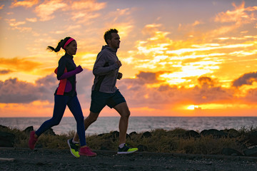 Running people training cardio together active friends jogging in early morning dawn sunrise on beach. Run fit couple runners woman and man running outdoor. Silhouettes of two athletes working out. Fotomurales