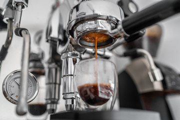 Coffee machine pouring single shot espresso in double wall glass from bottomless naked portafilter. Professional equipment at home or cafe.