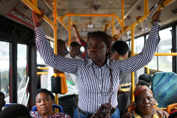 Abisoye Adeniyi, 23, stands in a moving bus as she goes to work in Lagos