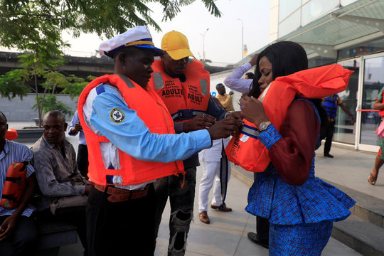 A Lagos State Ferry Service (LAGFERRY) official assists a passenger in wearing a life jacket at the Five Cowries Terminal in Falomo Lagos