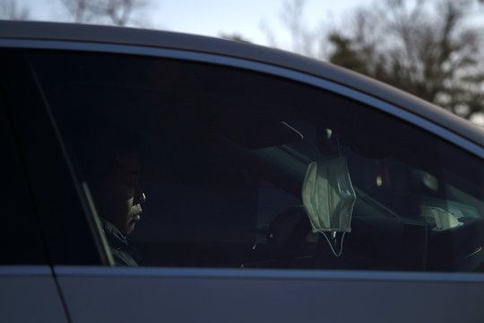 A face mask hangs from a car's rear-view mirror as a man drives on a street, following an outbreak of the novel coronavirus in country, in Beijing