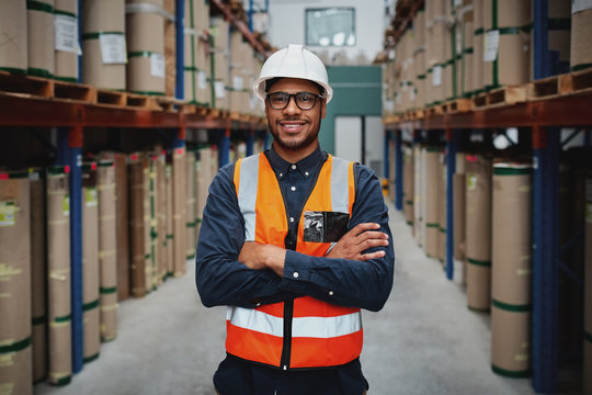 Portrait smiling worker wearing orange vest and white helmet with arms crossed in a large warehouse smiling