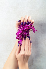 Stylish trendy purple female manicure. Woman hands are holding orchid flowers