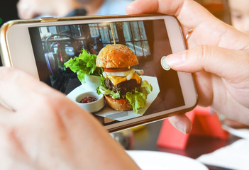 Selective focus smartphone picture which woman hands takes photography by smartphone of hamburger with fresh vegetables in the restaurant