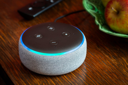 BATH, UK - FEBRUARY 17, 2020 : Close up of a 3rd generation Amazon Echo Dot glowing blue on a table in a domestic environment