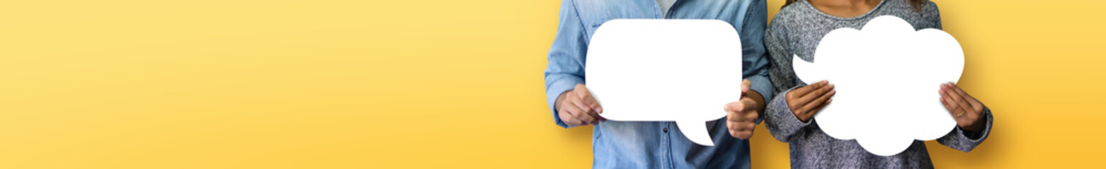 Couple holding white Speech Bubbles on yellow or orange isolated background. Banner, panoramic view for web.