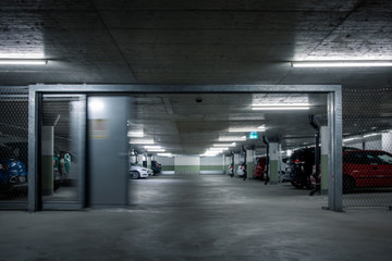 Gated underground parking. Cars parked in a garage with no people. Many cars in parking garage interior. Underground parking with cars (color toned image) Fototapete