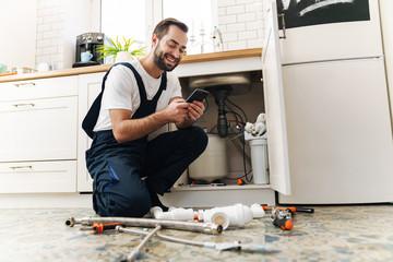 Man plumber work in uniform indoors using mobile phone. Wall mural