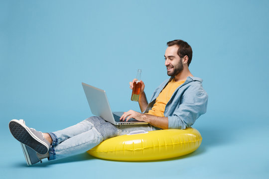 Smiling traveler tourist man in yellow clothes isolated on blue background. Passenger traveling abroad on weekend. Air flight journey concept. Sit in inflatable ring, work on laptop, hold beer bottle.
