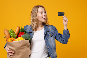 Excited young girl in denim clothes isolated on orange background. Delivery service from shop or restaurant concept. Hold brown craft paper bag for takeaway mock up with food product credit bank card.
