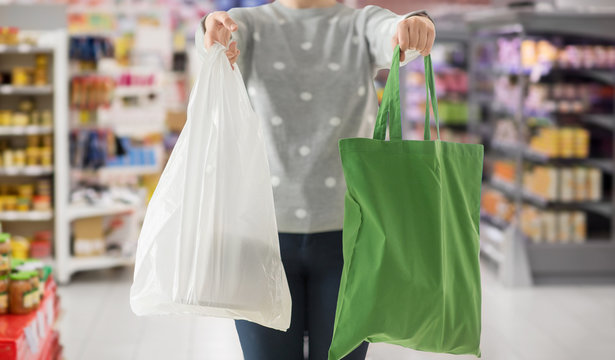 consumerism and eco friendly concept - woman holding reusable canvas tote for food shopping and plastic bag over supermarket on background